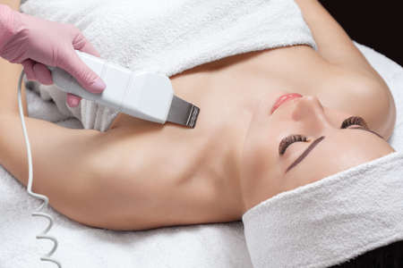 The doctor-cosmetologist makes the apparatus a procedure of ultrasound cleaning of the decollete skin of a beautiful, young woman in a beauty salon. Cosmetology and professional skin care. Stock Photo