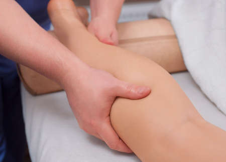 The doctor-podiatrist does an examination and massage of the patients legs Stock Photo