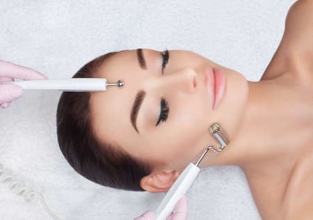 The cosmetologist makes the apparatus a procedure of Microcurrent therapy of a beautiful, young woman in a beauty salon. Cosmetology and professional skin care. 写真素材