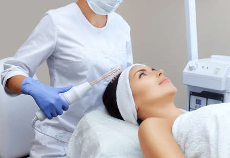 The doctor-cosmetologist makes the procedure Microcurrent therapy On the hair of a beautiful, young woman in a beauty salon.Cosmetology and professional skin care.