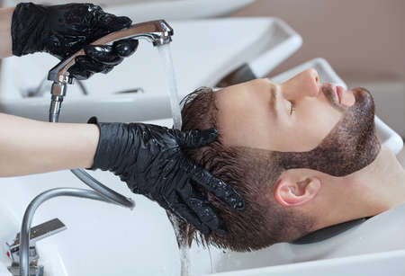 The hairdresser washes the head of the young man with shampoo after haircuts in the hairdresser.