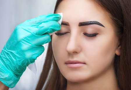 Master corrects makeup and gives shape and color to the eyebrows with henna in a beauty salon