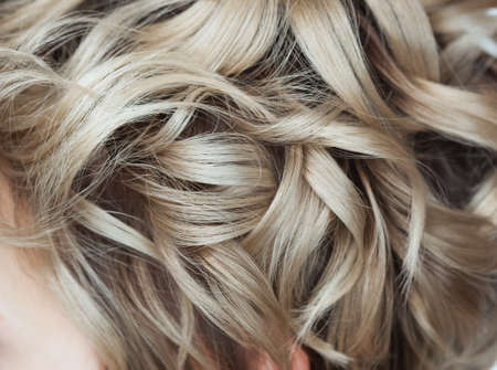 Curly blond hair close-up. Professional hair care.