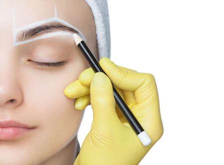 Maquillaje permanente para cejas de mujer hermosa con cejas gruesas en salón de belleza. Closeup esteticista haciendo tatuajes de cejas. Foto de archivo