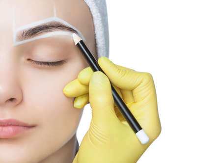 Permanent make-up for eyebrows of beautiful woman with thick brows in beauty salon. Closeup beautician doing  tattooing eyebrow. Foto de archivo
