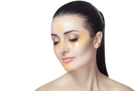 Collagen gold patches on the skin of the eyelid, forehead and chin on the face of a beautiful woman. Archivio Fotografico - 100755059