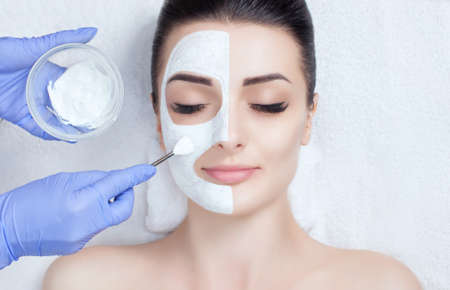 The cosmetologist for the procedure of cleansing and moisturizing the skin, applying a mask with stick to the face of a young woman in beauty salon. Cosmetology and professional skin care. 免版税图像
