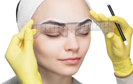 Permanent make-up for eyebrows of beautiful woman with thick brows in beauty salon. Closeup beautician doing  tattooing eyebrow. Banque d'images