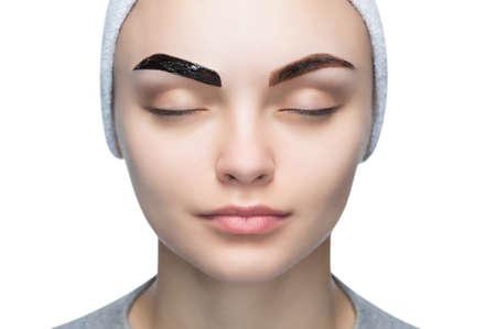 Retrato de una mujer con cejas hermosas y bien cuidadas, maquilladora aplica pintura henna en las cejas en un salón de belleza. Cuidado profesional de cejas, teñido y maquillaje permanente.