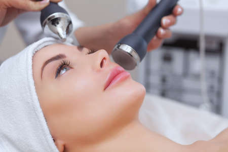 The cosmetologist makes the procedure an ultrasonic cleaning of the facial skin of a beautiful, young woman in a beauty salon.Cosmetology and professional skin care.