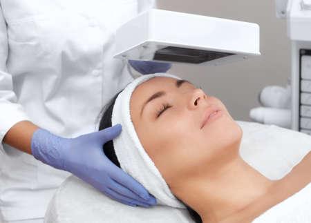 Il cosmetologo utilizza la lampada di legno per una diagnosi dettagliata delle condizioni della pelle. Il dispositivo rileva la presenza di malattie della pelle o aree infiammate. Cosmetologia e cura professionale. Archivio Fotografico