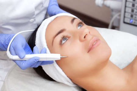 The cosmetologist makes the procedure treatment of Couperose of the facial skin of a beautiful, young woman in a beauty salon.Cosmetology and professional skin care.