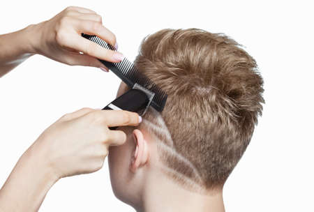 A hairdresser does a haircut for a young man in a  barbershop. Standard-Bild