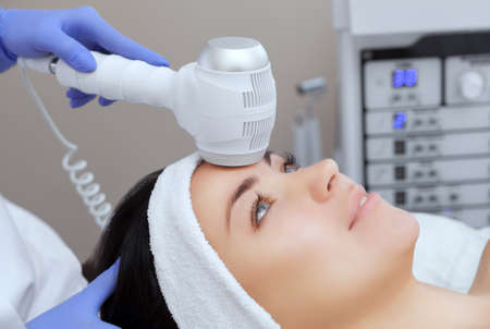 The doctor-cosmetologist makes the Cryotherapy procedure of the facial skin of a beautiful, young woman in a beauty salon.Cosmetology and professional skin care.