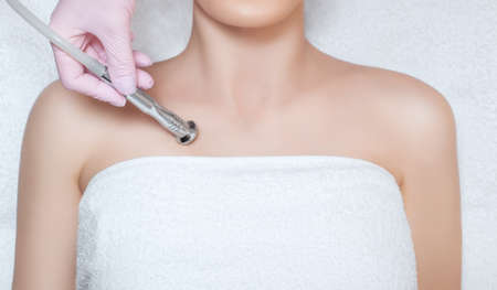 The cosmetologist makes the procedure Microdermabrasion of the décolletage skin of a beautiful, young woman in a beauty salon.Cosmetology and professional skin care.