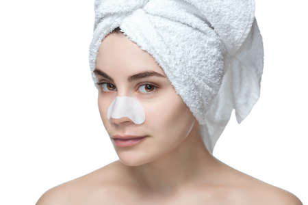 Portrait of a beautiful girl with a mask from acne on the nose after shower. Skin care at home.