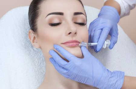 Der Arzt Kosmetiker macht Lippenvergrößerungsverfahren einer schönen Frau in einem Schönheitssalon. Kosmetologie Hautpflege. Standard-Bild