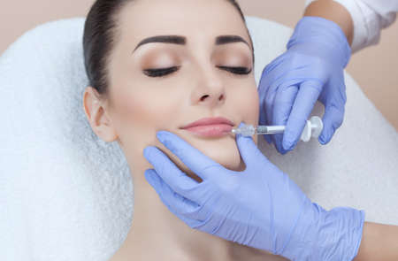 The doctor cosmetologist makes Lip augmentation procedure of a beautiful woman in a beauty salon.Cosmetology skin care. 版權商用圖片
