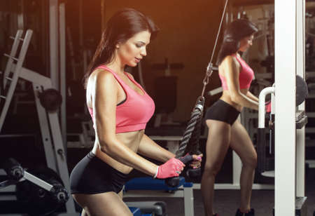 Slim, bodybuilder girl, does the exercises standing in front of the mirror in the gym. Sports concept, fat burning and a healthy lifestyle. Stockfoto