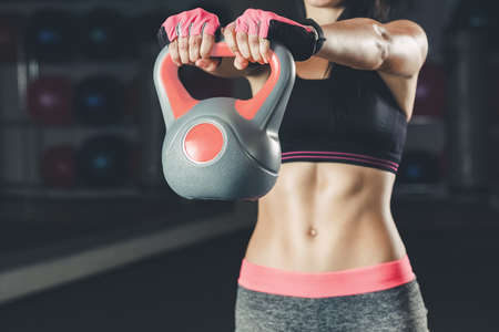 Slim, bodybuilder girl, lifts heavy dumbbell while training in the gym. Sports concept, fat burning and a healthy lifestyle.