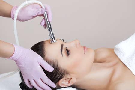 La cosmétologue fait la procédure Microdermabrasion de la peau du visage d'une belle jeune femme dans un salon de beauté. Cosmétologie et soins de la peau professionnels.