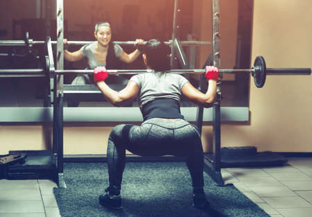 Slim girl bodybuilder lifting heavy barbell standing in front of the mirror while training in the gym. Sports concept, fat burning and a healthy lifestyle. Imagens