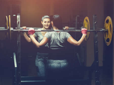 Slim girl bodybuilder lifting heavy barbell standing in front of the mirror while training in the gym. Sports concept, fat burning and a healthy lifestyle. Foto de archivo