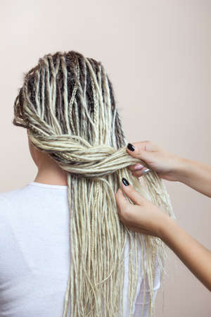 A hairdresser weaves dreadlocks to a beautiful young girl in a hairdresser's. Stock Photo