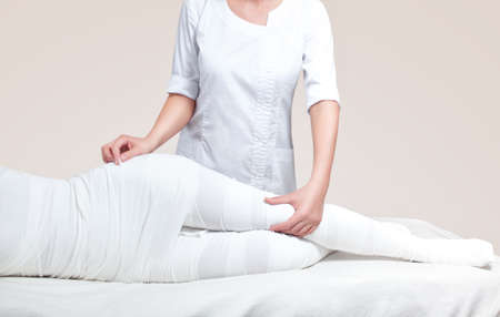 The cosmetologist wraps the leg of the customer. Anti-cellulite procedure-STYX wrap. 写真素材