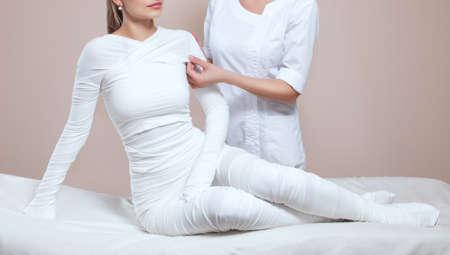 The cosmetologist wraps the leg of the customer. Anti-cellulite procedure-STYX wrap. Banco de Imagens