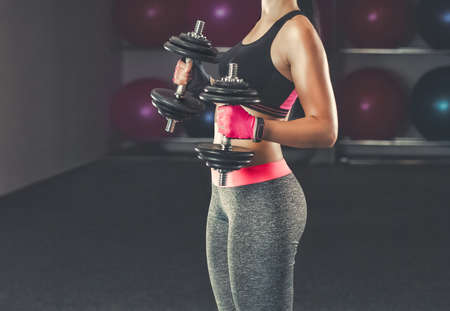Slim, bodybuilder girl, lifts heavy dumbbell standing in front of the mirror while training in the gym. Sports concept, fat burning and a healthy lifestyle. Imagens