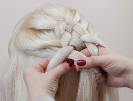 Beautiful girl with blonde hair, hairdresser weaves a  braid close-up, in a beauty salon. Professional hair care and creating hairstyles. Stock Photo