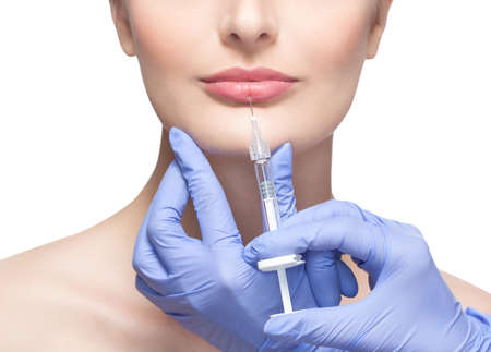 Lekarz kosmetolog wykonuje zastrzyk botoksu w usta pięknej kobiety w gabinecie kosmetycznym. Kosmetyka pielęgnacja skóry.