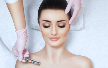 The cosmetologist makes the procedure Microdermabrasion on the collarbone and neck of a beautiful, young woman in a beauty salon.Cosmetology and professional skin care.