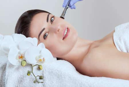 Le cosmétologue fait une procédure de microdermabrasion de la peau du visage d'une belle jeune femme dans un salon de beauté. Cosmétologie et soins de la peau professionnels. Banque d'images