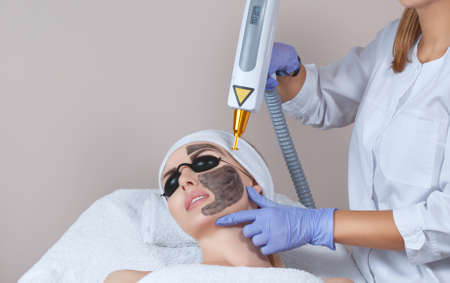 Carbon face peeling procedure in a beauty salon.