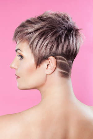 Portrait of a beautiful blonde woman with beautiful make-up and short haircut after dyeing hair in a hairdressing salon on a pink background. Stock Photo