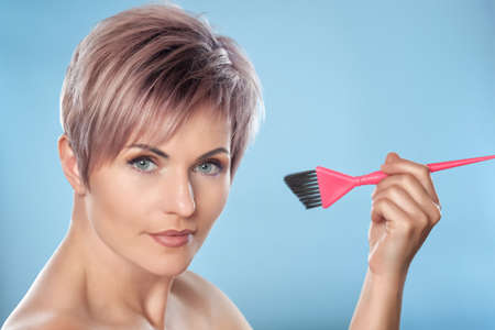 Portrait of a beautiful blonde with beautiful make-up and Kare haircuts for short hair holding a hair dye brush in a hairdressing salon on a blue background. Stock Photo