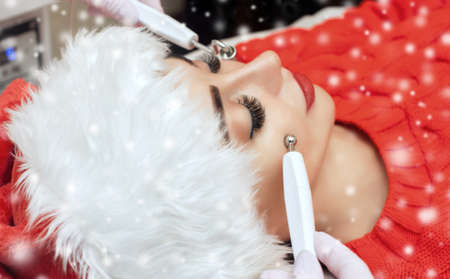 The cosmetologist makes the  procedure of Microcurrent therapy of a woman in Santa Claus hat 免版税图像