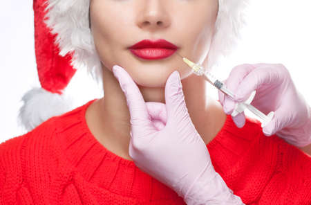 The doctor cosmetologist makes injection on the lips of a beautiful woman in the Santa Claus hat.
