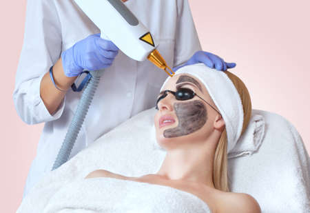 A girl doing carbon face peeling procedure in a beauty salon.