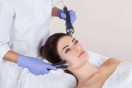 The cosmetologist makes the procedure of an ultrasonic cleaning of the facial skin of a beautiful, young woman in a beauty salon. Stock Photo
