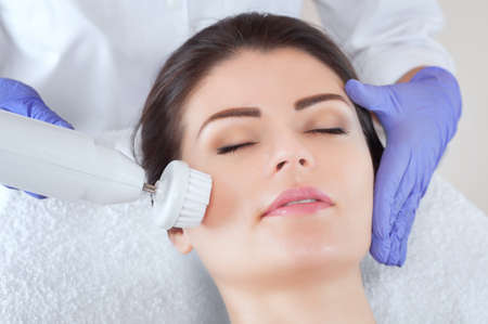The cosmetologist is doing the procedure of cleaning facial skin of a beautiful, young woman in a beauty salon. Stock Photo