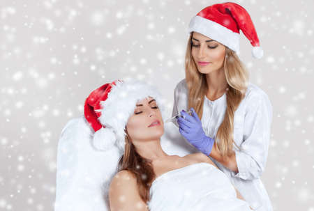 The doctor cosmetologist makes  injection on the face skin and lips of a beautiful, young woman in the Santa Claus hat.