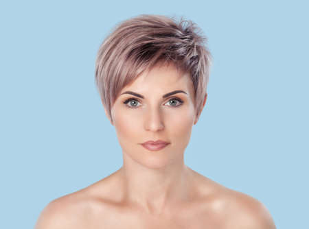 Portrait of a beautiful blonde woman with beautiful make-up and short haircut after dyeing hair in a hairdressing salon on a blue background.