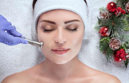Il cosmetologo sta eseguendo la procedura di pulizia della pelle del viso di una bella e giovane donna