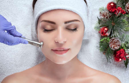 The cosmetologist is doing the procedure of cleaning facial skin of a beautiful, young woman