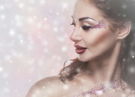 A young woman with creative makeup and beautiful hairstyle, on the background of snowflakes. New Year's concept.