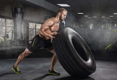 Young adult man flipping and rolling tire during exercise in the gym. Sports concept, fat burning and a healthy lifestyle. 写真素材