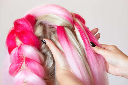 The hairdresser weaves braids with pink kanekalons beautiful blonde beauty salon. Archivio Fotografico